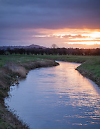 Sunrise at the River Brue on the Somerset Levels, with Glastonbury Tor seen in the distance