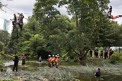 Denham, UK. 24th July, 2020. Environmental activists from HS2 Rebellion, including Swan (l) and Larch (r) on a line above the shallow river Colne, try to protect an ancient alder tree from destruction in connection with works for the HS2 high-speed rail link in Denham Country Park. A large policing operation involving the Metropolitan Police, Thames Valley Police, City of London Police and Hampshire Police as well as the National Eviction Team was put in place to enable HS2 to remove the tree.