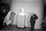 07/06/1964<br /> 06/07/1964<br /> 07 June 1964<br /> Bust of President Kennedy unveiled at the American Embassy, Dublin. A bust of the late President John F. Kennedy was unveiled by Mrs Ted Sorensen, in the presence of the retiring American Ambassador to Ireland, Mr. Matthew McCluskey. The bust was set in the main hall of the new United States Embassy, Ballsbridge. Mrs Sorensen was the four day bride of Mr. Ted Sorensen, who was a special aide to the late President. Image shows Mrs Sorensen unveiling the bust in the presence of the Ambassador. Mr. Sorensen is on the left.
