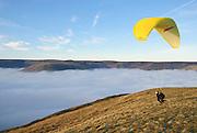 A Paraglider soars form Mam Tor above a misty Edale