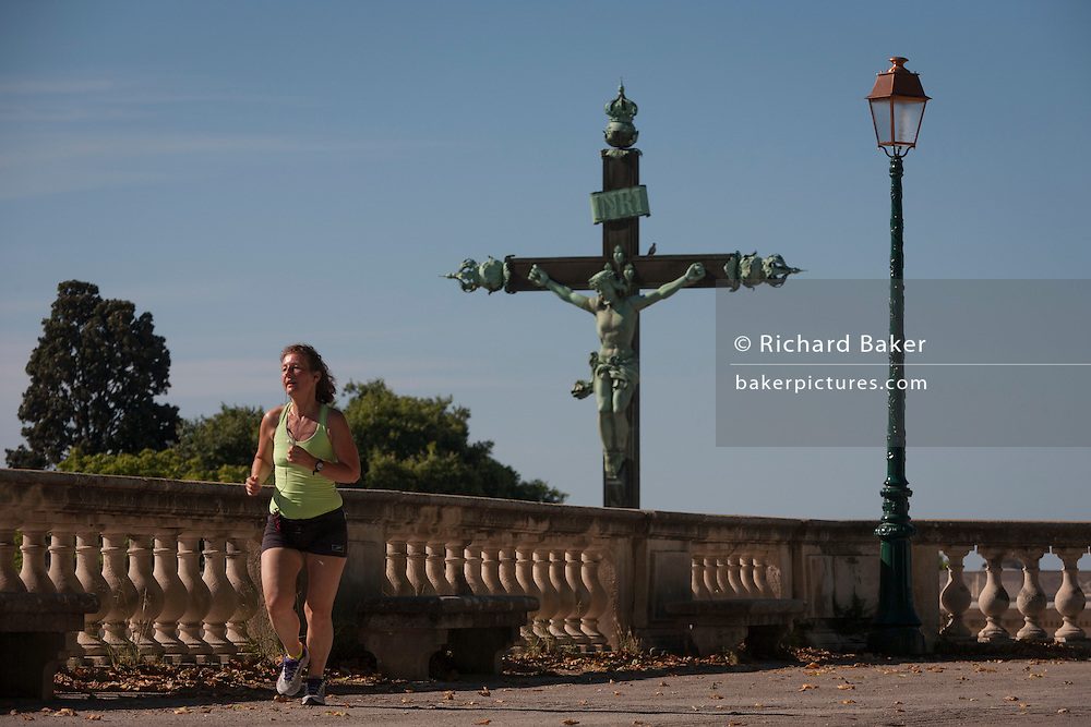 A crucified Christ on the cross and local jogger in Place du Peyrou, Montpellier, south of France.
