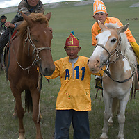 MONTOLIA. Young, costumed riders after a 20km race at a traditional naadam festival on a remote pass in Arbulag Sum, near Muren in Hovsgol Aimag, Mongolia.