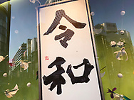"""May 2, 2019, Tokyo, Japan: As Japan entered the Reiwa Era, the Wako Department Store, a landmark of Tokyo's famed Ginza shopping district ushered in new era by displaying a calligraphy work of the kanji characters """"Reiwa"""" in it's main window. This was brushed by shodo master Japanese artist Hakkou Ishitobi. Underneath the artwork was a golden plaque that read """"In Celebration of Enthronement: We offer our sincere congratulations to his Majesty the Emperor upon his accession"""". Japan's Emperor Akihito abdicated the Chrysanthemum Throne bringing an end to the Heisei Era (1989 - 2019). The new era called 'Reiwa"""" began May 1, 2019 when Crown Prince Naruhito ascended the throne. The two kanji characters """"'rei"""" and """"wa"""" can be translated as """"fortunate harmony"""" or """"peace in harmony"""" were taken from a stanza about plum blossoms in Man'yoshu, a collection of Japanese poetry written sometime after 759. Japanese calendars years are based upon the reigns of it's emperor's. Photo by Torin Boyd."""