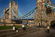 Geese and people relaxing on a warm evening during the lockdown by Tower Bridge at 6pm on 9th April 2020 in London, United Kingdom. Normally crowded with people leaving work the City of London is like a ghost town as workers stay home during the Coronavirus pandemic.
