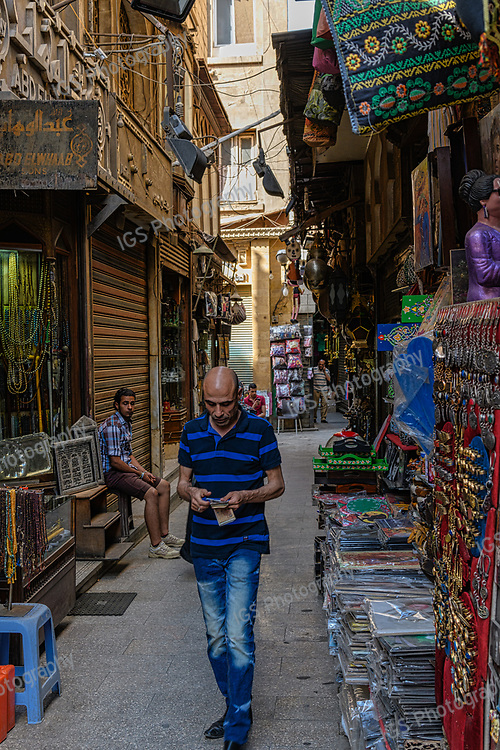 Potential customer walks past an Egyptian vendor as he waits  patiently for customers in his shop in Khan El-Khalili market