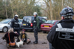 Harefield, UK. 16 January, 2020. Enforcement agents working on behalf of HS2 watch over Stop HS2 activist Mark Keir after preventing him from reentering the Harvil Road wildlife protection camp in the Colne Valley after it was agreed that he could bring out dogs to a woman waiting outside belonging to a fellow activist evicted earlier in the morning from the camp after over two days and two nights spent in a tree in woodland.