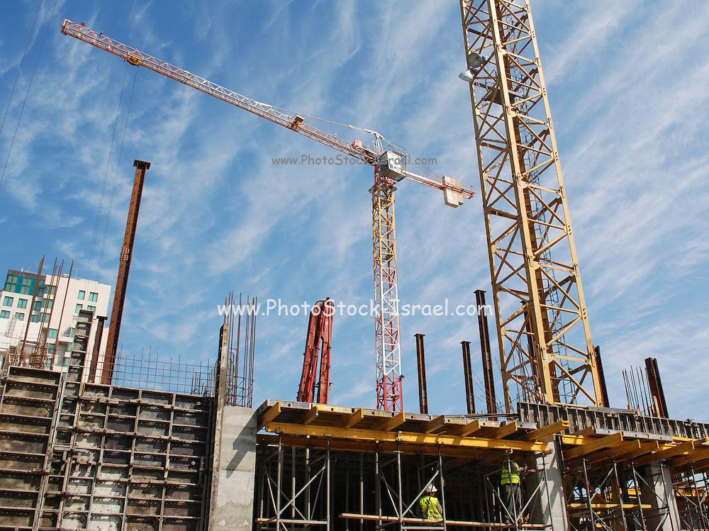 Israel, Tel Aviv, High Rise construction site tower crane lifting iron rods