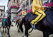 Italy, Siena, the Palio: from right Acquila, SElva, Oca.  the horses enetered the square ready for the race. At the shot of the mortaretto, the horses come out of the Entrone and line up at the starting line, known as the mossa. As soon as the last horse reaches the starting line the race begins and lasts for three rounds of the square (about 1 kilometre in total). The first horse to cross the finishing line is the winner, regardless of whether it is still mounted.