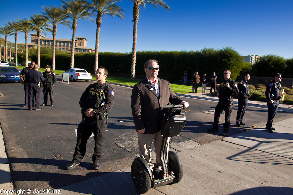 30 NOVEMBER 2011 - PHOENIX, AZ:    The chief of security at the Westin Kierland Resort and Spa uses a Segway scooter to get around while he and Phoenix police watch anti-ALEC protesters at the gate to the resort Wednesday. About 300 people picketed the American Legislative Exchange Council (ALEC) conference at the Westin Kierland Resort and Spa in Phoenix, AZ, Wednesday. The protesters claim ALEC, a conservative think tank, violates its tax exempt status by engaging in lobbying, a charge ALEC officials deny. Many conservative pieces of legislation, like Arizona's anti-immigration bill SB1070, originate with ALEC conferences (SB 1070 originated at an ALEC conference several years ago). Many of the protesters are also members of the Occupy movement.  PHOTO BY JACK KURTZ
