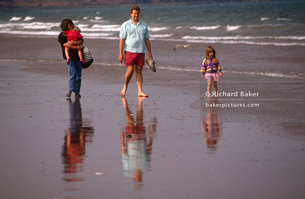 A family walk along the surf with their reflections in wet sand at the Welsh seaside town of Llandudno. Holding a very tired toddler, the mother walks alongside the father and a small girl who splashes in shallow water. Their figures are seen in the reflected wet sand at low tide.