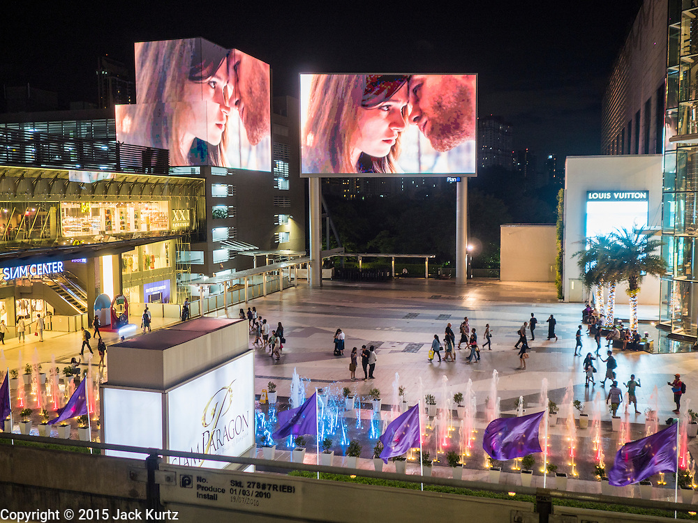 20 MAY 2015 - BANGKOK, THAILAND: People walk under huge illuminated billboards between Siam Paragon and Siam Center malls. Bangkok's malls consume more electricity than some provinces. Siam Paragon, a popular high end mall in central Bangkok, consumes nearly twice as much electricity at the northern province of Mae Hong Son. Thais and foreigners alike flock to the malls in Bangkok, which are air conditioned. Most of the electricity consumed in Bangkok is generated in Laos and Myanmar. In 2013, the Bangkok Metropolitan Region consumed about 40 per cent of the Thailand's electricity, even though the BMR is only 1.5 per cent of the country's land area and about 22 per cent of its population.   PHOTO BY JACK KURTZ