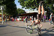 BMX rider performs abalance trick during a busking show to earn some money on the Southbank, London, UK. The South Bank is a significant arts and entertainment district, and home to an endless list of activities for Londoners, visitors and tourists alike. This is also London's home of urban / street sports.