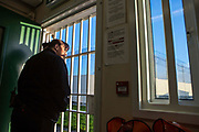 A prison officer looks out of the gated doorway to one of the industrial units inside HMP/YOI Portland, a resettlement prison with a capacity for 530 prisoners. Dorset, United Kingdom.