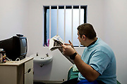 A prisoner reading a newspaper in his cell. HMP Wandsworth, London, United Kingdom.