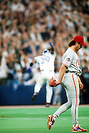 TORONTO, ONTARIO, CANADA - OCTOBER 23: Pitcher Mitch Williams of the Philadelphia Phillies walks off the field as Joe Carter of the Toronto Blue Jays jumps for joy in the background after Carter hit a World Series winning walk off home run in Game Six of the 1993 World Series at the Skydome on October 23,1993 in Toronto, Ontario, Canada. The Blue Jays won the game 8-6, winning the Series 4-2.  (Photo by Ron Vesely)