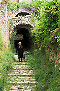 Albania, Dhermi, mature woman in the narrow alley