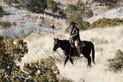 Cowboy on horseback riding up slope of hill, Ladder Ranch, west of Truth or Consequences, New Mexico, USA.