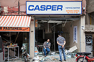 Turkish shop owners stand outside their stores and survey the damage to the buildings after a double car bombing in Reyhanli, a Turkish border town with Syria.