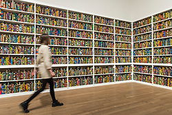 "© Licensed to London News Pictures. 08/04/2019. LONDON, UK.  A staff member walks by British-Nigerian artist Yinka Shonibare's artwork ""The British Library"", 2014, which has been acquired by Tate Modern.  Comprising 6,328 books, covered in wax fabric and gold foil, 2,700 books have the names of first or second generation immigrants to Britain on the spine.  Photo credit: Stephen Chung/LNP"