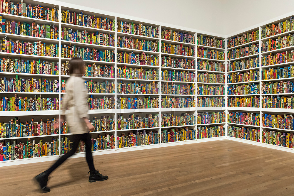 """© Licensed to London News Pictures. 08/04/2019. LONDON, UK.  A staff member walks by British-Nigerian artist Yinka Shonibare's artwork """"The British Library"""", 2014, which has been acquired by Tate Modern.  Comprising 6,328 books, covered in wax fabric and gold foil, 2,700 books have the names of first or second generation immigrants to Britain on the spine.  Photo credit: Stephen Chung/LNP"""