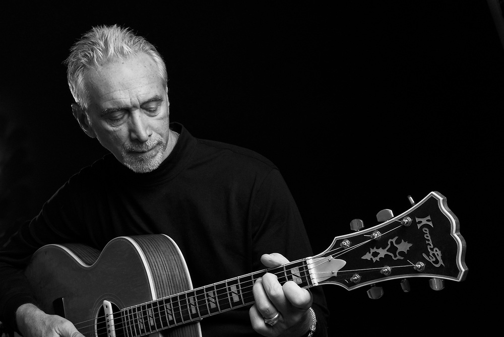 Black and white portrait of a musician playing the guitar in the studio against a black background.