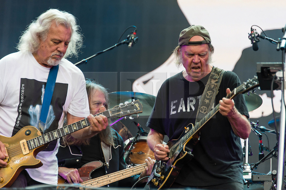 """© Licensed to London News Pictures. 12/07/2014. London, UK.   Neil Young and Crazy Horse performing live at Hyde Park as part of the British Summer Time series of outdoor concerts.In this picture - Neil Young (right), Frank Sampredo (left), Rick Roses (centre).   Crazy Horse is a rock band long associated with Neil Young,  consisting of members Rick Roses, (bass, vocals), Ralph Molina (drums, vocals), Frank """"Poncho"""" Sampedro ( guitar, organ, keyboards).  Photo credit : Richard Isaac/LNP"""