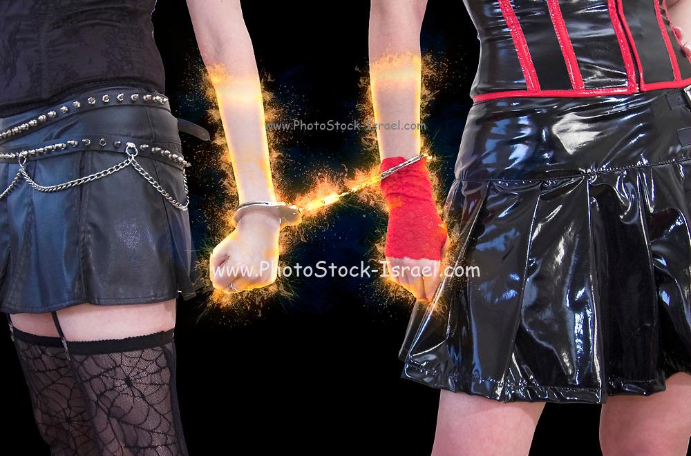 2 women wearing vinyl cloths handcuffed to each other