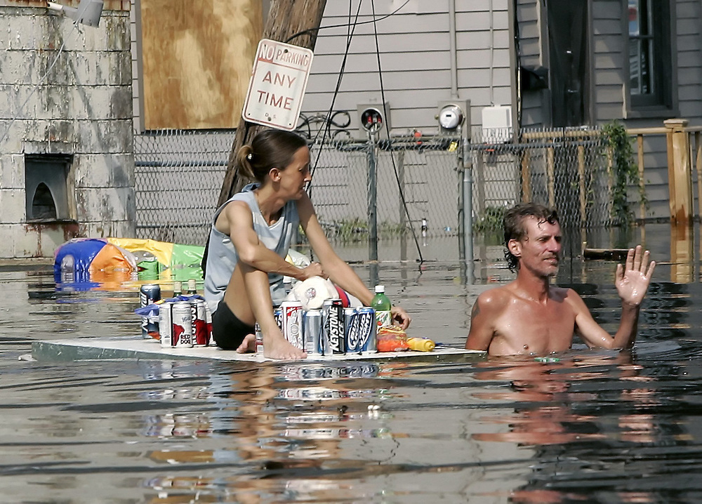 A man, dragging a woman on a floating door with supplies, waves off a rescue boat in flooded New Orleans August 30, 2005.  Hurricane Katrina devastated the town and surroundings and looting was reported in the area. Floodwaters engulfed much of New Orleans on Tuesday as officials feared a steep death toll and planned to evacuate thousands remaining in shelters after the historic city's defenses were breached by Hurricane Katrina. REUTERS/Rick Wilking
