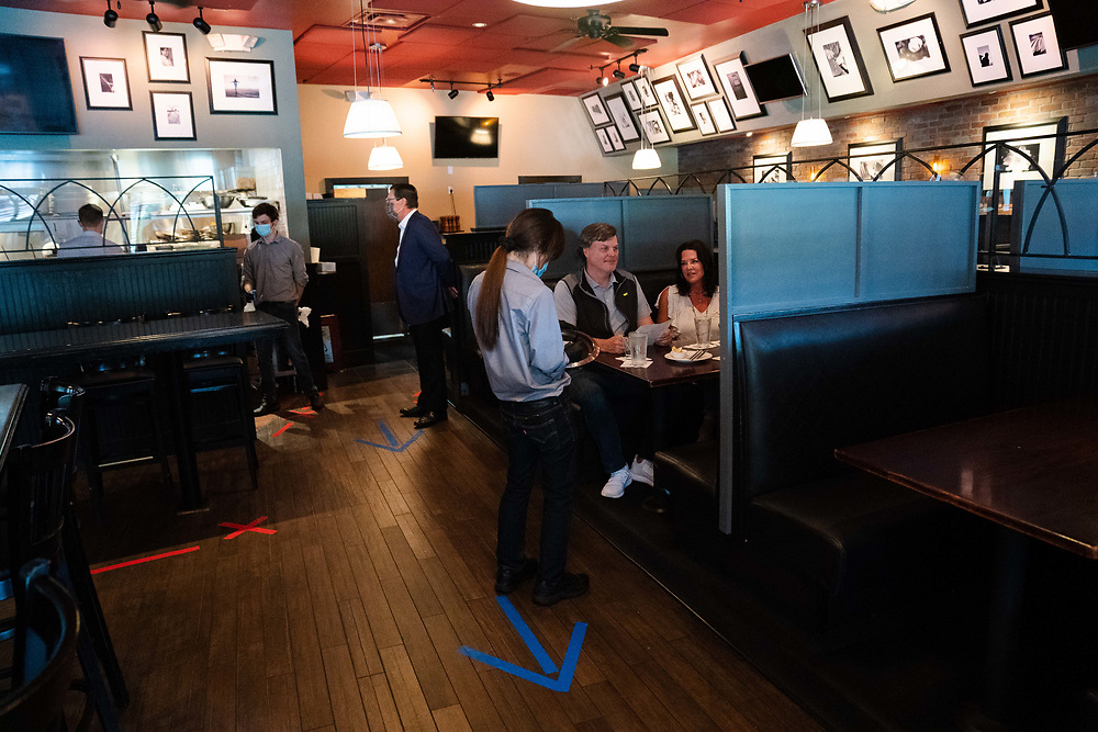 """JOHNS CREEK, GA - APRIL 29: The Callicutt family (from left): Jack, Torey, and their 18-year-old daughter, Caroline (not pictured), dine at Marlow's Tavern. Sam Boger, a server, takes their order. The restaurant placed raised dividers between each of the booths to help prevent the spread of coronavirus.<br /> <br /> The family has been coming to the establishment for more than 10 years and was excited to be back after the restaurant reopened today.<br /> <br /> """"We couldn't wait to come back,"""" said Torey Callicutt. Torey and Caroline ordered the Royale with Cheese and Jack had the Cuban sandwich.<br /> <br /> (Photo by Kevin D. Liles for The Washington Post) https://wapo.st/3bVKDT5"""