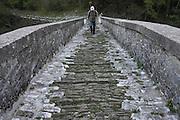 Greece, Epirus, Zagori, Pindus Mountains, Tourist walking across an old disused Arched Stone Bridge