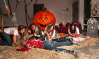 "Andrea Selesky, Gwen Huot, Brianna Healey, Haven Gilbert and Hannah Forston (as the dead body) represent the senior class for their ""Halloween"" themed hallway during Homecoming festivities moved indoors due to the inclement weather Friday evening.  (Karen Bobotas/for the Laconia Daily Sun)"
