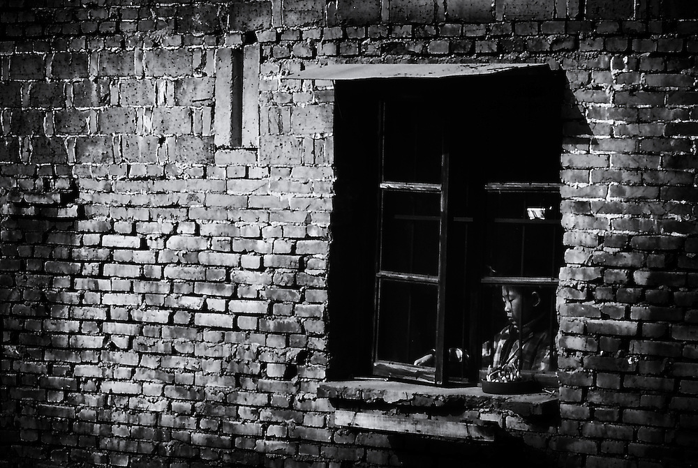 Young chinese pupil at the window. Suzhou, China.