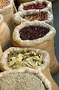 Israel, Tel Aviv, Bags of spices and herbs awaiting clients at the spice market in Lewinski street September 2005