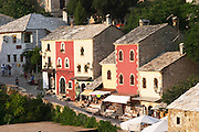 The busy old market bazaar street Kujundziluk with lots of tourist craft and art shops and street merchants. Traditional style houses renovated after the war. Historic town of Mostar. Federation Bosne i Hercegovine. Bosnia Herzegovina, Europe.
