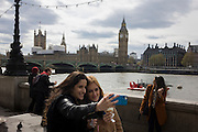 Two young women take a selfie overlooking the River Thames on London's Southbank with the Palaces of Westminster and Queen Elizabeth Tower containing Big Ben bell in the background.