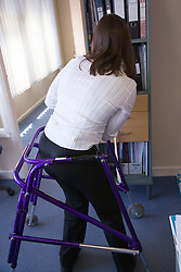 Young woman with walking frame doing some filing in an office,