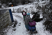 Roma women walking to their a home, a squat in the snow in one of the largest Roma encampments 'bidounvilles' outside Paris. Winter, Sarcelles, Paris suburbs, France<br /><br />Eastern european Roma migrants, often from Romania and Bulgaria, searching for better opportunities, they move near to western european cities. They typically are poor and live in squats, here around the periphery of Paris, in the suburbs 'banlieu' where they typically build ramshackle homes from recycled wooden panels and corrugated iron, or sometimes benders made from branches covered in tarpaulins. They live in woods and forest, industrial estates or derelict buildings. Life is especially difficult for them in the harsh conditions of winter and rain. Most of these camps get destroyed by police and Roma are eventually evicted, some deported back home or moving on to build another home. They often survive by recycling metal and electronic goods, selling recycled clothes and objects they find in trash bins, or through begging or playing music on the city streets or inside metro stations. Paris, France