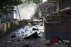 © Licensed to London News Pictures. 14/06/2017. London, UK. A fireman's hose rests near a walkway filled with debris directly under Grenfell Tower on the Lancaster West Estate -  scene of a huge fire in west London. The blaze engulfed the 27-storey building with 200 firefighters attending the scene. A number of fatalities have been reported. Photo credit: Peter Macdiarmid/LNP