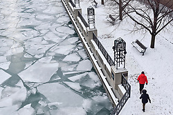 © Licensed to London News Pictures. 31/12/2017. CHICAGO, USA.  People walk alongside the Chicago River which has frozen during a period of sub-zero temperatures.  Extremely cold conditions are forecast to continue into the New Year. Photo credit: Stephen Chung/LNP