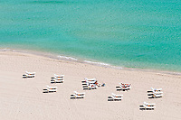 Aerial view of a beach in the caribbean with tourists relaxing.