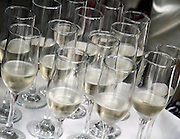 Flutes of champagne rest on serving tray with white linen cloth.
