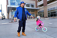 """Edward Zayas, Jr., of Allentown, walk with his stepdaughter Avery Green, 4, as she rides her bike near the PPL Center in Allentown, Pennsylvania. Zayas is a chef at Union & Finch bistro and has been working a lot to accommodate the increasing demand for takeout and delivery orders. """"We came out let her ride on the sidewalk where it's easier with no people, Zayas says, """"Normally I wouldn't do this. I have been talking with family in Newark, New Jersey and they are on lock down. We just had to get out."""" Communities across the Lehigh Valley are adjusting to life during the coronavirus pandemic that is impacting the daily lives of Pennsylvania residents both socially and economically. (Photo by Matt Smith)"""