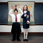 School age boy and girl pose with awards in classroom.