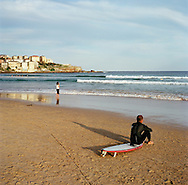 Surfer on the beach in the late afternoon at Bondi Beach, Sydney, NSW, Australia