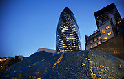 Construction of new towers in The City of London at night. 1 St Mary Axe, also knowns as The Gherkin stands with a new clear view as rubble from a building once there stands in a pile. This iconic building is one of the best loved buildings in London with it's distinctive bullet like shape and twisted glass exterior.
