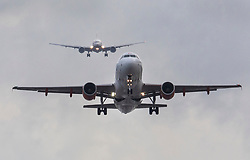 © Licensed to London News Pictures. 21/12/2018. Gatwick, UK. An aircraft takes off from Gatwick, as another (top) approaches for landing, as flights resume. Further delays are expected today after two days of disruption due to multiple sightings of drones over the airfield. Thousands of passengers have been stranded as flights have been cancelled or diverted. Police are still hunting the drone operator. Photo credit: Peter Macdiarmid/LNP