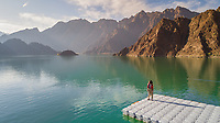 Aerial view of a woman standing in front of the Hatta Lake in Dubai, U.A.E.