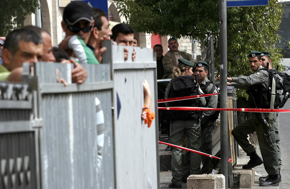 Palestinians and Arab-Israeli men stand behind a fence as Israeli border police officers (right) block the road where an Arab man stabbed an ultra-nationalist Israeli rabbi in front of Jerusalem's Old City Damascus gate on March 18, 2008.