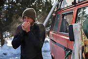 Mark Kielpinski, of Brewster, MA, tries to warm up his hands after surfing at Green Harbor in Marshfield, MA, on a cold February day.