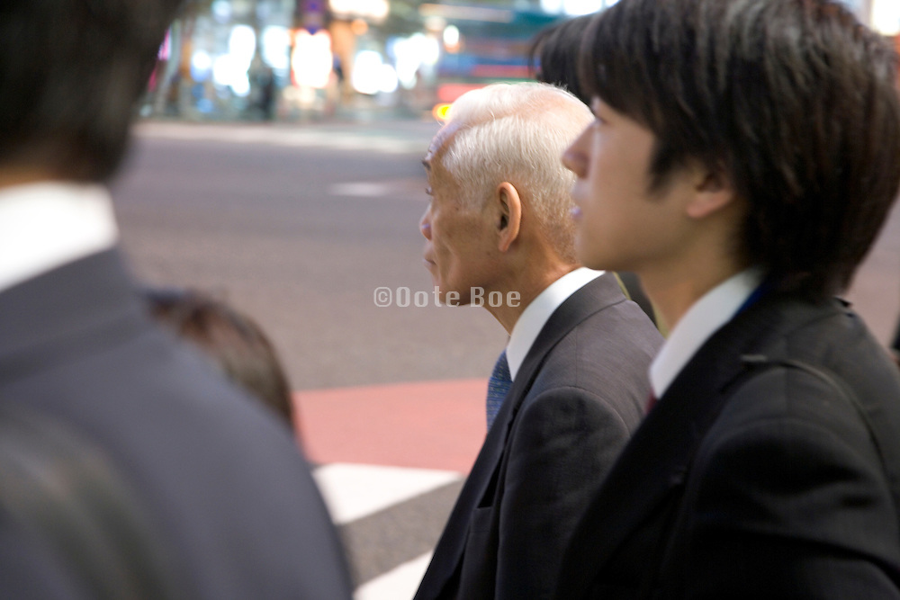 a young and elderly businessman waiting at a crossing for the light to turn green